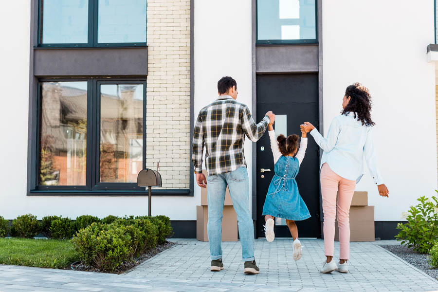 Personal Insurance - Young Family in Front of Their New Home Jumping